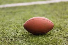 Boule de football américain de rugby se trouvant sur le champ vert image stock