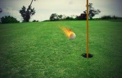 Boule de golf ardente près du trou dans un domaine d'herbe photographie stock