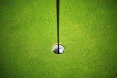 Boule de golf au trou Photographie stock