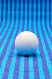 Boule de golf blanche sur la table rayée bleue Images libres de droits