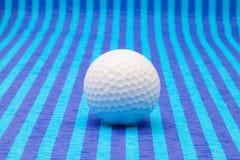 Boule de golf blanche sur la table rayée bleue Photographie stock libre de droits