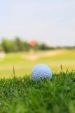 Boule de golf dans l'herbe rugueuse Photo stock