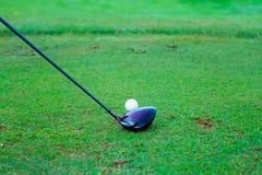 Boule de golf derrière le conducteur au champ d'exercice, abondance du copie-espace a Images stock