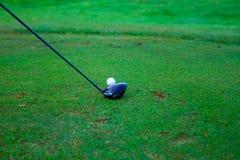 Boule de golf derrière le conducteur au champ d'exercice, abondance du copie-espace a Photographie stock