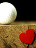 Boule de golf et coeur au bord de table Photos libres de droits