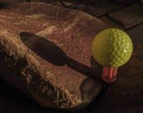 Boule de golf jaune sur la pièce en t de brosse placée entre les roches images stock