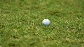 Boule de golf mettant sur l'herbe verte près du golf de trou pour gagner dans le jeu au terrain de golf avec le fond de tache flo photographie stock
