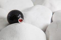 Boule de golf noire et coeur rouge Image stock