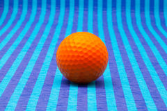 Boule de golf orange sur la table rayée bleue Photographie stock