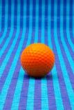 Boule de golf orange sur la table rayée bleue Image stock