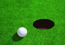 Boule de golf près de trou avec l'espace de copie Images stock