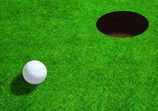 Boule de golf près de trou avec l'espace de copie Photographie stock libre de droits