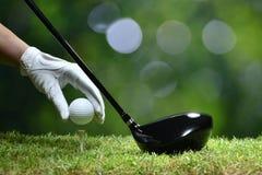 Boule de golf de prise de main avec la pièce en t images libres de droits