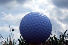 Boule de golf sur la pièce en t dans la fin d'extrémité sous le ciel bleu image stock