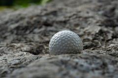 Boule de golf sur la roche images stock