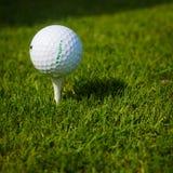 Boule de golf sur une pièce en t contre le terrain de golf avec l'espace de copie Photos libres de droits
