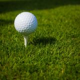 Boule de golf sur une pièce en t contre le terrain de golf avec l'espace de copie Photographie stock libre de droits