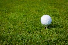 Boule de golf sur une pièce en t contre le terrain de golf avec l'espace de copie Photographie stock