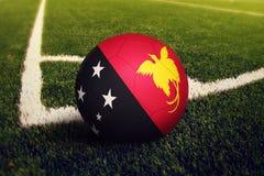 Boule de la Papouasie-Nouvelle-Guin?e sur la position de coup-de-pied faisant le coin, fond de terrain de football Th?me national photographie stock libre de droits
