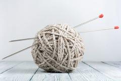 Boule de laine avec des rais pour le tricotage fait main sur la table en bois Pointeaux de tricotage de laines et de tricotage Image libre de droits
