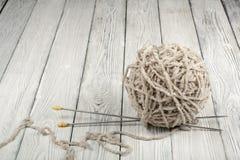 Boule de laine avec des rais pour le tricotage fait main sur la table en bois Pointeaux de tricotage de laines et de tricotage Images stock