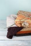 Boule de laine, d'aiguilles et de chandail de laine avec des rais pour le tricotage fait main dans le panier sur la table en bois Photographie stock libre de droits