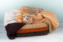 Boule de laine, d'aiguilles et de chandail de laine avec des rais pour le tricotage fait main dans le panier sur la table en bois Image stock