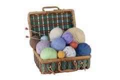 Boule de laine, d'aiguilles et de chandail de laine avec des rais pour le tricotage fait main dans le panier sur la table en bois Photos libres de droits