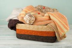 Boule de laine, d'aiguilles et de chandail de laine avec des rais pour le tricotage fait main dans le panier sur la table en bois Photo libre de droits
