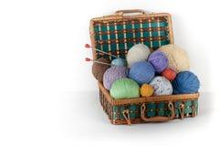 Boule de laine, d'aiguilles et de chandail de laine avec des rais pour le tricotage fait main dans le panier sur la table en bois Photo stock