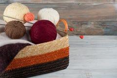 Boule de laine, d'aiguilles et de chandail de laine avec des rais pour le tricotage fait main dans le panier sur la table en bois Photographie stock