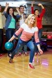 Boule de lancement de jeune femme heureuse dans le club de bowling Photo libre de droits
