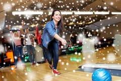 Boule de lancement de jeune femme heureuse dans le club de bowling Photographie stock