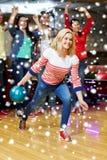 Boule de lancement de jeune femme heureuse dans le club de bowling Photo stock