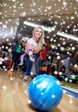 Boule de lancement de jeune femme heureuse dans le club de bowling Image stock