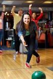 Boule de lancement de jeune femme heureuse dans le club de bowling Photos stock
