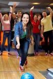 Boule de lancement de jeune femme heureuse dans le club de bowling Photos libres de droits