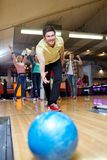 Boule de lancement de jeune homme heureux dans le club de bowling Photos libres de droits