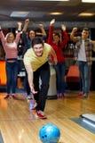 Boule de lancement de jeune homme heureux dans le club de bowling Photos stock