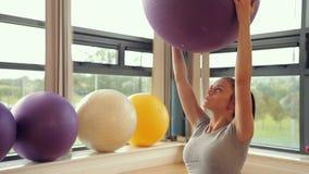 Boule de levage d'exercice de femme sportive de brune banque de vidéos