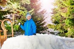 Boule de neige de jet de petit garçon se cachant derrière le mur de neige Images stock