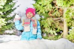 Boule de neige de jet de petite fille se cachant derrière le mur de neige Photo libre de droits