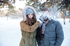 Boule de neige thowing de femme d'une manière amusante dans son visage d'ami Photographie stock libre de droits