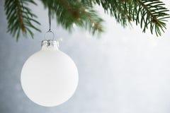 Boule de Noël blanc sur l'arbre de Noël sur le fond de bokeh de scintillement Carte de Joyeux Noël Images stock