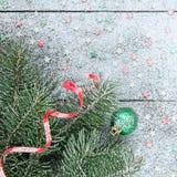 Boule de Noël et arbre de Noël verts sur le vieux fond en bois neigeux Photos libres de droits