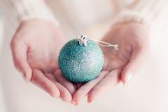 Boule de Noël sur des mains Photographie stock