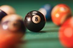 Boule de piscine avec le numéro 8 au-dessus du fond vert Photo libre de droits
