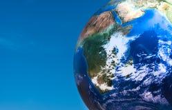 Boule de planète de concept de jour de terre au-dessus de ciel bleu image libre de droits