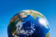 Boule de planète de concept de jour de terre au-dessus de ciel bleu photos libres de droits