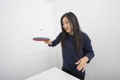 Boule de rebondissement femelle de joueur de ping-pong sur la palette photographie stock